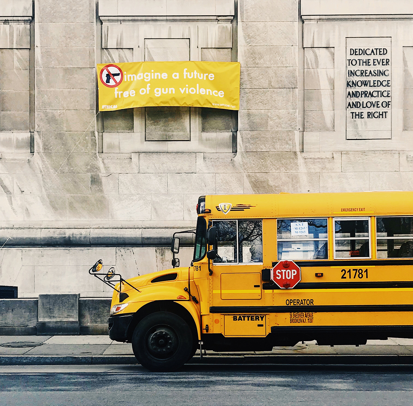bus driving past an anti-gun banner